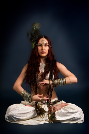 Performance. Young attractive retro model in old-fashioned wild clothing dancing. Tribe. Tattoo. Native savage woman photo