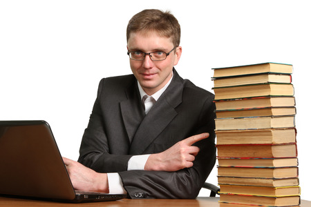 shrugs: young guy working at a laptop and shrugs off paper books