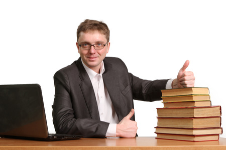 A young guy can not determine the choice where to get information from a laptop or paper books isolated on white