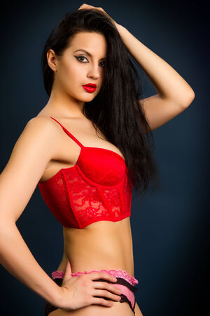 Yung beautiful brunette woman in red lingerie on dark background photo