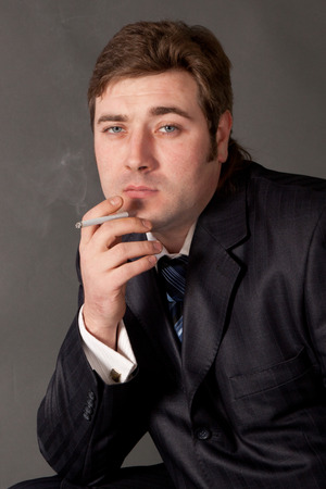 a man in a business suit smoking a cigarette on a gray background photo