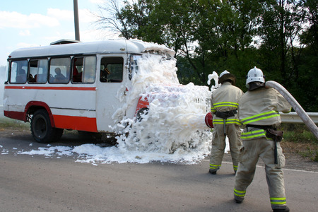 firefighters in gas masks with foam extinguish a burning bus photo