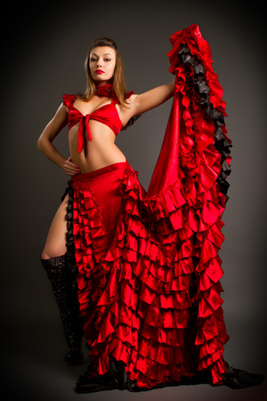 Close-up photo of the lady in gypsy costume dancing flamenco  on a gray background