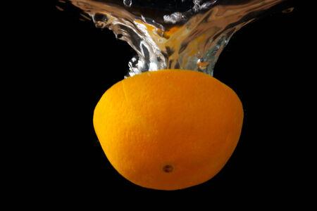 half orange with splashes of water on a black background photo