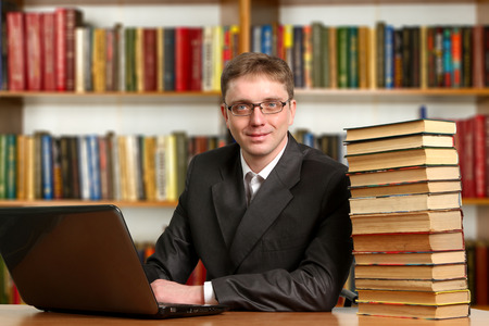Portrait of clever student with open book reading it in college library photo