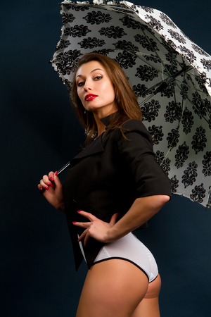 beautiful young brunette with a white umbrella on a dark background