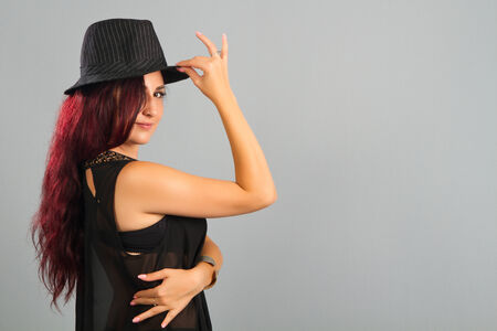 Sexy girl wearing a black hat, isolated on grey photo