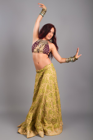 Beautiful girl belly dance movement, Young beautiful belly dancer in a  golden costume photo