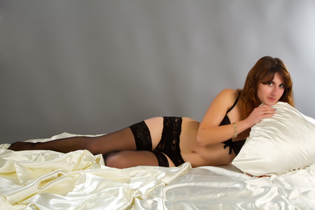 Young beautiful Sexy woman wearing elegant lingerie posing on bed photo