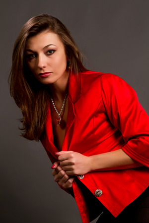 beautiful young brunette in a red jacket on a gray background photo