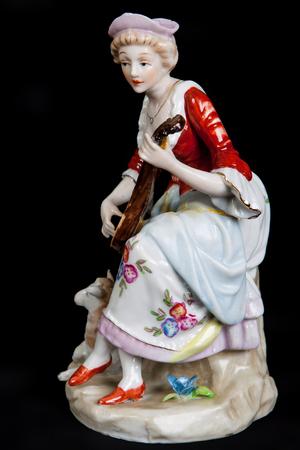 medieval dress: figura de porcelana en forma de una chica en traje medieval aislado en un fondo negro Foto de archivo