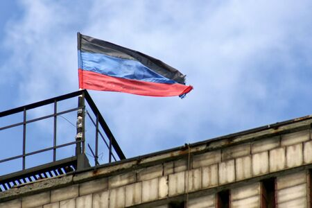 Donetsk Republic flag located on one of the buildings of Donetsk on background the sky