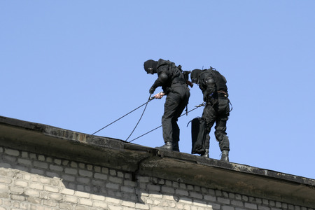 antiterrorist: Subdivision anti-terrorist police during a black tactical exercises. Rope Techniques. Real situation. Stock Photo