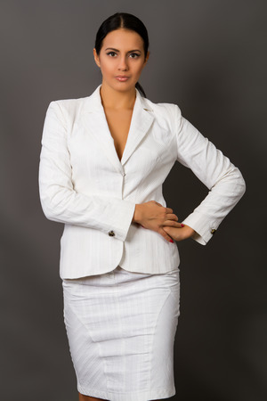 attractive  female: beautiful young brunette in a white business suit on a gray background