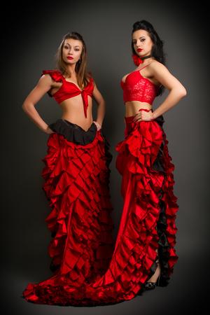 bailando flamenco: foto de primer plano de los dos dama en traje de baile flamenco gitano en un fondo gris Foto de archivo