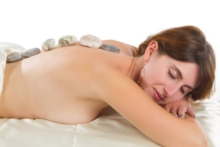 hot rock therapy: young woman receves stone therapy Beautiful young woman having a massage in a spa Stock Photo