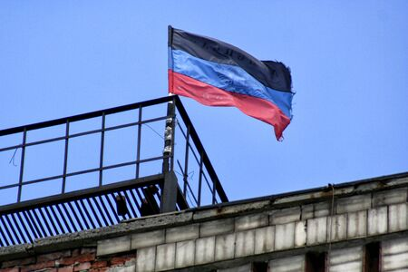 proclaimed: Donetsk Republic flag located on one of the buildings of Donetsk on background the sky