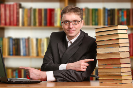 Portrait of clever student with open book reading it in college library Stock Photo