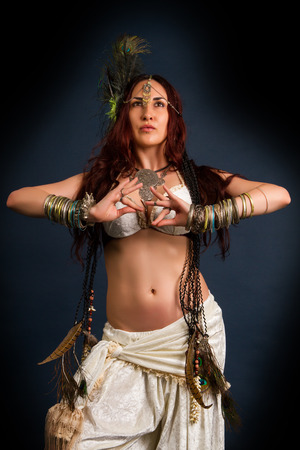 Performance. Young attractive retro model in old-fashioned wild clothing dancing. Tribe. Tattoo. Native savage woman Stock Photo
