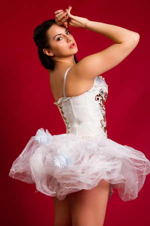 beautiful young girl in a white sexy dress on a red background photo