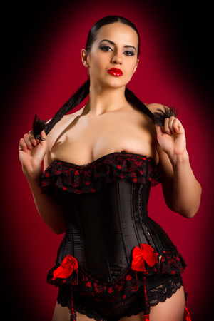 closeup portrait of a sexy young woman in black corset and touching her breast against red  background photo