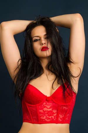 Yung beautiful brunette woman in beautiful red lingerie on dark background photo