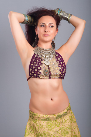 Beautiful girl belly dance movement, Young beautiful belly dancer in a  golden costume Stock Photo
