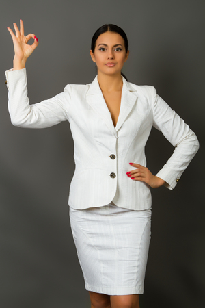 beautiful young brunette in a white business suit on a gray background photo