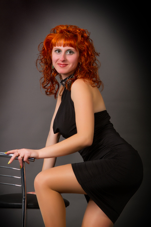 Beautiful young red-haired girl in a black dress on a gray background photo