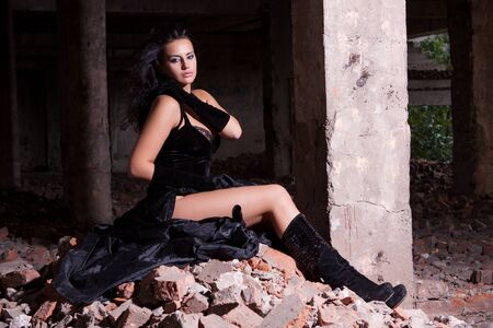 Young beautiful woman posing in ruins after fire photo