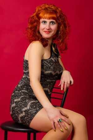 beautiful young red-haired girl  in an elegant dress on a red background photo