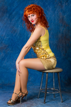 Beautiful young red-haired girl in a yellow dress on a blue background photo