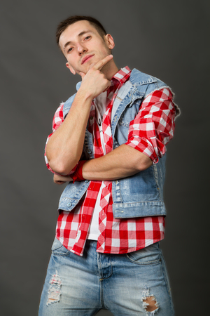 handsome young man in a denim vest on a gray background Standard-Bild