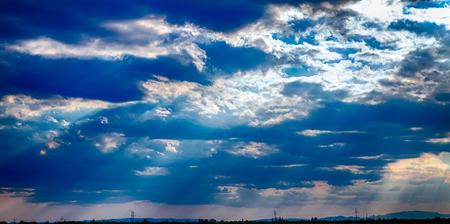 dramatic blue sky with clouds and sun rays meteorology concept