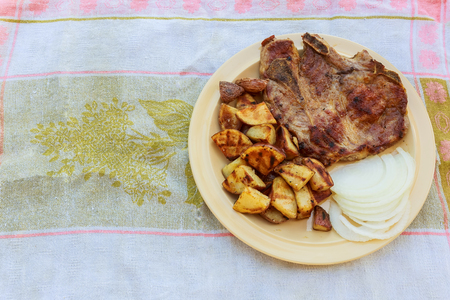 pork pork steak potato on a rural white onion potato in village