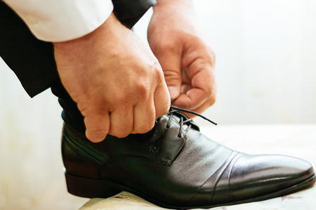 shoe laces: groom tying shoe laces groom hand shoes
