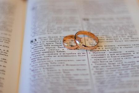Two wedding rings on a bible bible wedding rings Imagens
