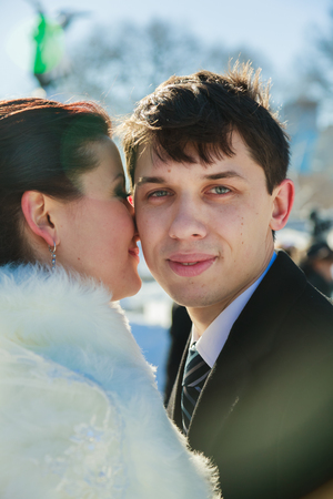 Young couple newlyweds walking in a winter forest in the snow. Bride and groom hugging in the park in winter. Beautiful man and woman in their wedding clothes are among the pines.
