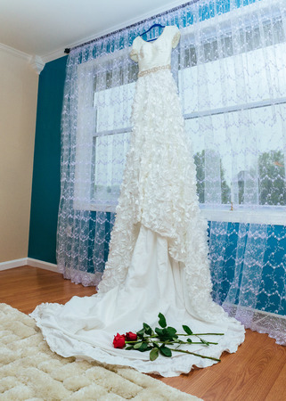 tenderly: The perfect wedding dress with a full skirt in the room wedding dress hold red rose Stock Photo
