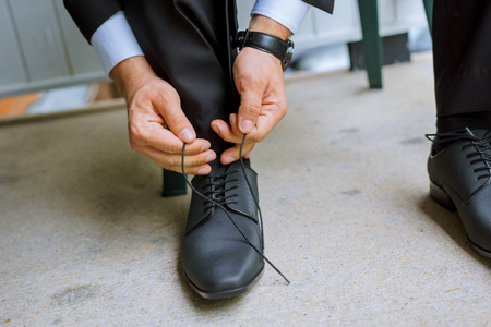 cuff link: Hands of wedding groom getting ready in suit putting his wedding shoes. Stock Photo