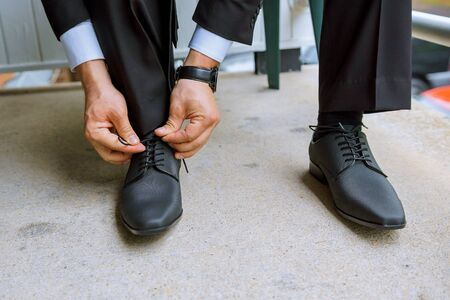 Hands of wedding groom getting ready in suit putting his wedding shoes. Stock Photo
