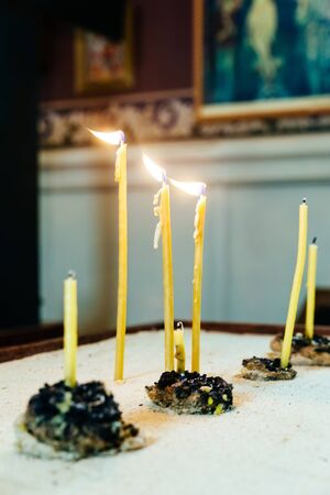 enlightening: lighting candles in a church church candles Stock Photo