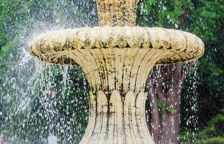water stream: Water fountain in park. Splashing streams of fountain in Water stream pouring from fountain. Fountain water splashing on water surface of park lake. Fountain in summer park.