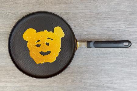 Pancakes with smile on wood background Pancake