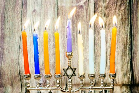 chanukiah: low key image of jewish holiday Hanukkah with menorah traditional Candelabra and wooden dreidels spinning top . glitter overlay