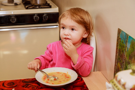 Girl-preschooler eats a tasty meal in cozy restaurant.