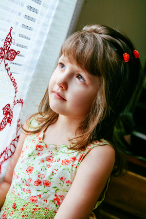 Sad little girl looking at window little girl looking out the window Stock Photo