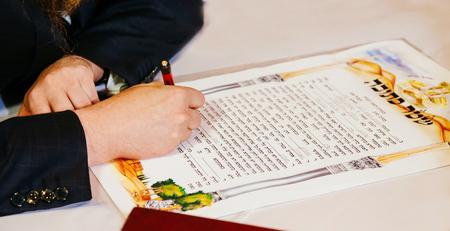 Traditionele Joodse bruiloft, het ondertekenen van huwelijkse voorwaarden ketubah. Joodse huwelijkscontract.