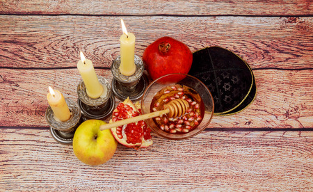 rosh hashanah jewesh holiday concept torah book, honey, apple and pomegranate over wooden table. traditional holiday symbols.