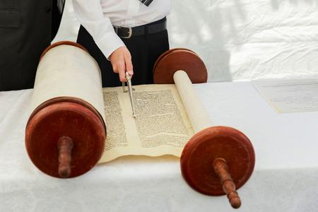 hebrew script: 5 SEPTEMBER 2016 USA NY Hand of boy reading the Jewish Torah at Bar Mitzvah Bar Mitzvah Torah reading